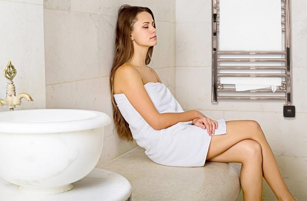 kvinna i badrumsmiljö med handdukstork